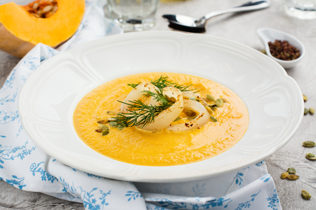 Homemade pumpkin and carrot soup with squid rings, seeds and dill Stock Photo