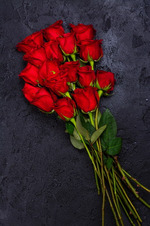 Bunch of red roses on black stone background. Copy space