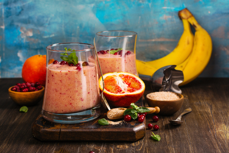 Healthy refreshing pink smoothie with apple, red oranges, cowberry and bran Standard-Bild