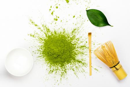 Green matcha tea powder and tea accessories on white background