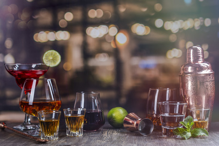 Assortment of different strong alcohol drinks on bar counter over night lights background. Copy space