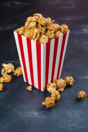 Caramel popcorn in a paper cup Фото со стока