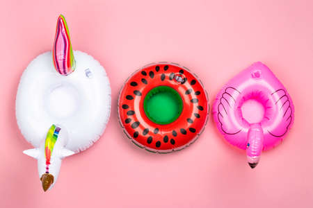 Various inflatable toy rings on pink background. Drinks holders for swimming pool party. Copy space
