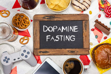 Dopamine fasting background. Life without social media, gadget and food detox concept. Red and white signal ribbon covering junk food and digital devices. Copy space