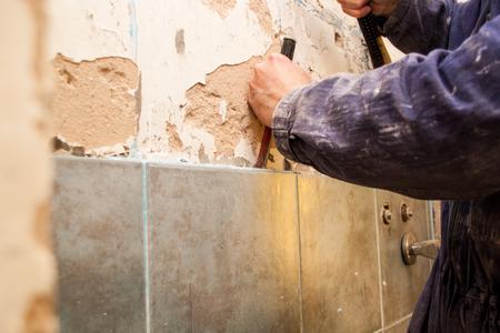 Rénovation de plats, céramiques, maîtres qui volent de vieilles tuiles dans la salle de bain avec un marteau Banque d'images