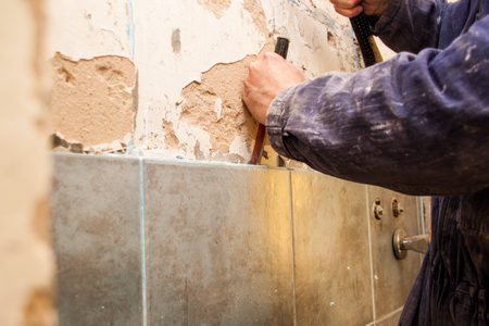Flat renovation, ceramics, master robbing old tiles in the bathroom with a hammer