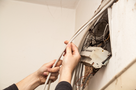 Flat renovation, handyman, electrician, trying to connect all the wires in the junction box, where the fuses Stock Photo