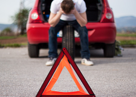 Car remained in trouble on the road, the red triangle placed behind the car, worried driver ran head