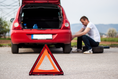 Car remained in trouble on the road, the red triangle placed behind the car, the driver concerned is trying to refuse to malfunction