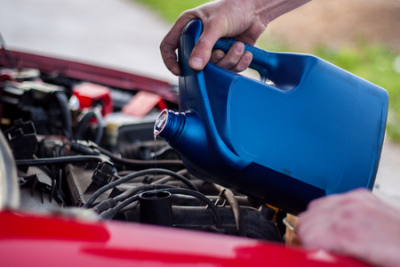 Raised the hood of the car, the master pours oil in the engine of the car Stock Photo