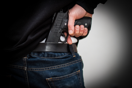 The man hid the gun behind their backs, robbery, crime, kidnapping