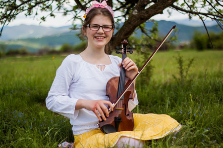 Beautiful blonde girl sitting on a beautiful green grass full of flowers and enjoy the sounds of the violin, girl playing the violin in the countryside on a beautiful meadow