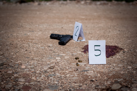 The crime scene, murder, investigation, gun and shell finds the police, puts tags rip shells and guns, traces of blood, gore, crime scene investigation Stock Photo