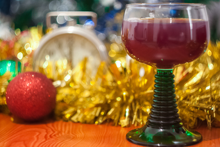 Christmas and New Year celebration holiday with glass of wine and red ball covered with yellow fir on the red table Stock Photo