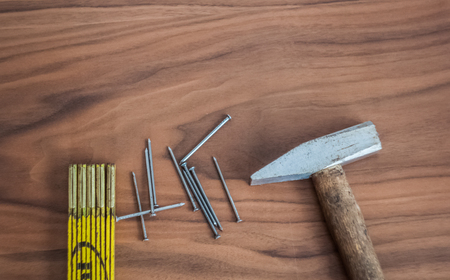 Hammer, nails and meter stick on a wooden table desk