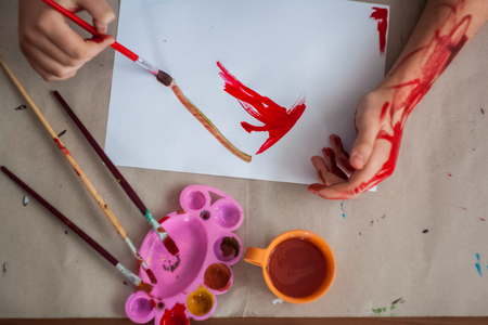 Girl painting with brush and colorful paint with paint smeared hands Stock Photo