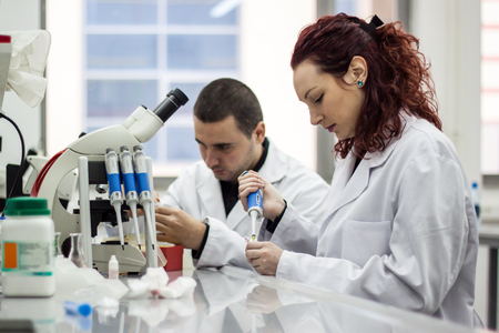 Modern scientist working with pipette in biotechnology laboratory equipment for research on a white table and an assistant who records the measured results