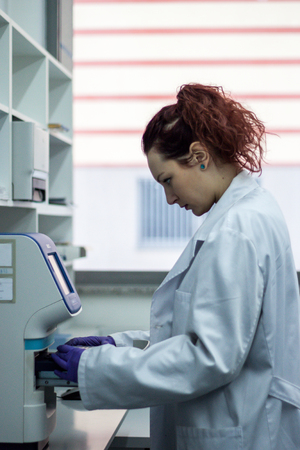 Scientist or researcher or PHD student take DNA samples from flask for analysis in a biotechnology laboratory