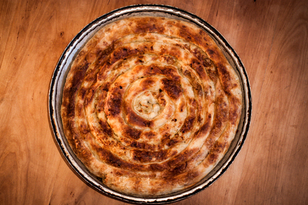 Traditional Bosnian Turkish dish, pork pie, pie in the pan on a nice wooden background