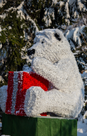 Decorative polar bear with reflection and red box as a gift in the sun and snow in nature, Christmas decoration