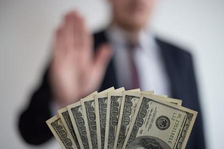 Bribe and corruption, offered cash to a businessman in a suit, does not want to take them, hold upright hands