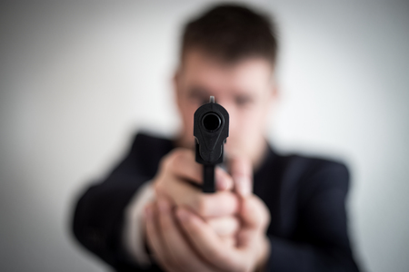 A thief in a suit with a gun directed at a man takes cash, hundreds of dollars are abducted with the help of a pistol, a crime, an armed robbery