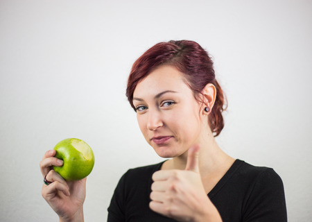 A young girl holds a battered apple in her hand, with a smile on her face, a white background, a studio, facial expressions