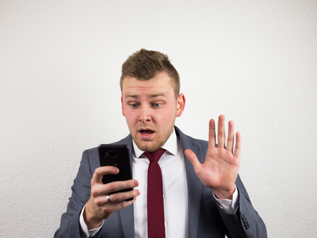 Young, caucasian and handsome businessman worried and surprised by a text message he got on the mobile and typing an answer to it.