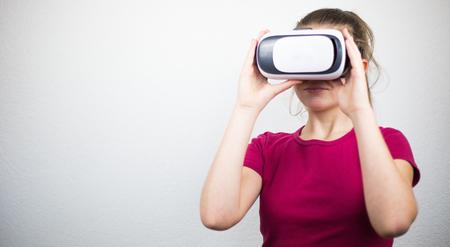 Teenager with virtual reality glasses on the head, enjoying watching, amazing technology, white background, studio Archivio Fotografico