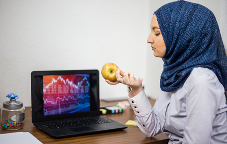 Imaginary covered young Muslim with hijab, in office, business and finance, laptop on office desk, economy, accounting