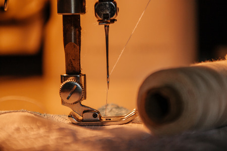 Sewing machine, sewing process, thread next to machines, pause to replace the thread, fabric is stitched