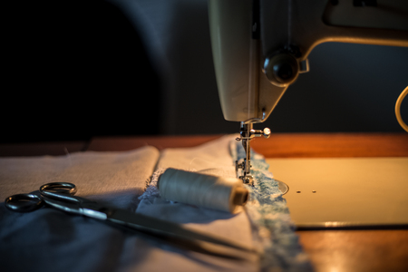 Sewing machine, sewing process, scissors and thread next to machines, pause to replace the thread, fabric is stitched