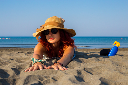 A young girl lying on the stomach on a beach in the sand, stretched out her hands, enjoying the sun and the sea, with a hat on her head and glasses