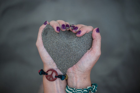 Girl keeps sand in hands in heart shape with cool and retro black and blue bracelets with peace sign and purple nails on the sandy beach Imagens