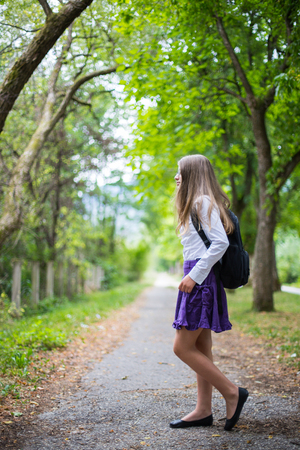 Pretty beautiful blonde child girl cheerful and happily walking across street back to school enjoying through alley in the nature with backpack, glasses, purple skirt and white shirt Stock Photo