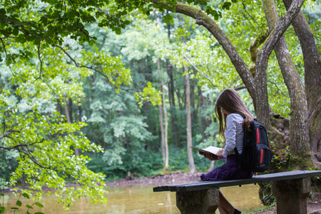 Pretty little blonde schoolgirl with backpack sitting on the bench in the nature park near lake and reading a book getting ready to go back to school in the nature studying for exam