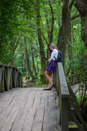 Pretty little blonde schoolgirl with backpack standing on a bridge in the nature and reading a book getting ready to go back to school in the nature studying for exam