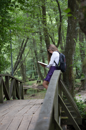 Pretty little blonde schoolgirl with backpack standing on a bridge in the nature and reading a book getting ready to go back to school studying for exam