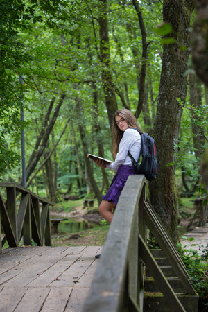 Pretty little blonde schoolgirl with backpack standing on a bridge in the nature and reading a book looking at the camera getting ready to go back to school studying for exam Zdjęcie Seryjne