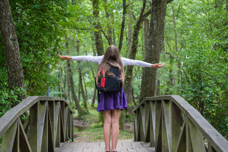 Beautiful pretty blonde school girl child with white shirt, purple skirt and backpack standing on the bridge in nature with arms widespread happily back to school