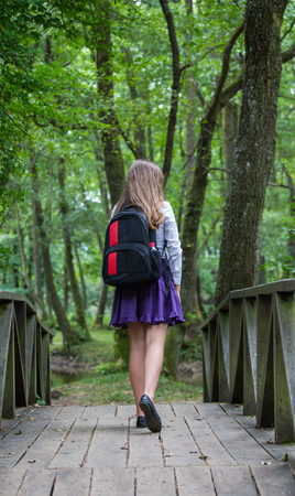 Beautiful pretty blonde school girl child with white shirt, purple skirt and backpack standing on the bridge in nature back to school