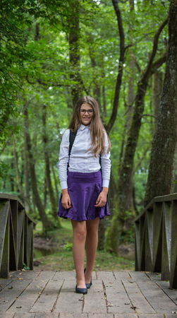 Beautiful pretty blonde school girl child smiling with glasses, white shirt, purple skirt and backpack standing on the bridge in nature back to school Zdjęcie Seryjne