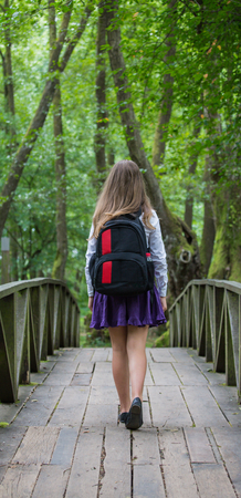 Beautiful pretty blonde school girl child from back with white shirt, purple skirt and backpack standing on a bridge in nature back to school Zdjęcie Seryjne