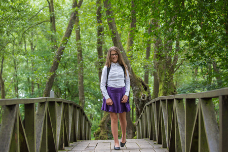 Beautiful pretty blonde school girl child cheerful smiling with glasses, white shirt, purple skirt and backpack walking on the bridge in nature back to school autumn