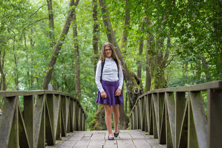 Beautiful pretty blonde school girl child smiling with glasses, white shirt, purple skirt and backpack taking a walk on the bridge in nature back to school autumn