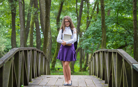 Beautiful pretty blonde school girl child cheerful smiling with glasses, white shirt, purple skirt and backpack standing on a bridge in nature holding notes and books back to school autumn Zdjęcie Seryjne