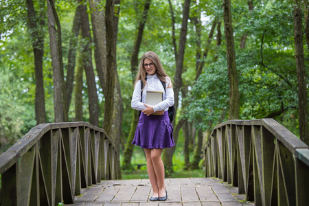 Beautiful pretty blonde school girl child smiling with glasses, white shirt, purple skirt and backpack standing on a wooden bridge in nature holding notes and books back to school autumn
