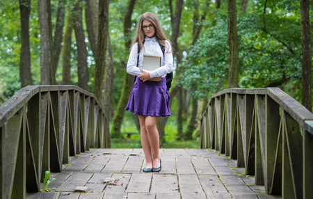 Beautiful pretty blonde school girl child smiling with glasses, white shirt, purple skirt and black backpack standing on a wooden bridge in nature holding notes and books back to school autumn