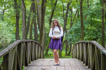 Beautiful pretty blonde school girl child smiling with glasses, white shirt, purple skirt and black backpack standing on a wooden bridge in nature trees holding notes and books back to school autumn Zdjęcie Seryjne