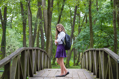 Beautiful pretty blonde school girl child smiling with glasses, white shirt, purple skirt and black backpack standing on a wooden bridge in nature trees holding books back to school autumn Zdjęcie Seryjne